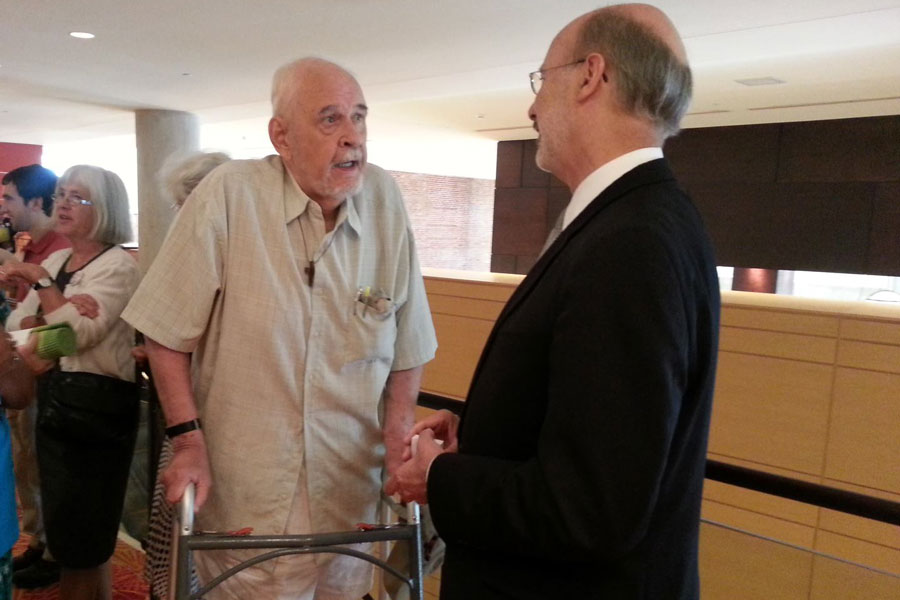 Tom Wolf speaks with a supporter at an event